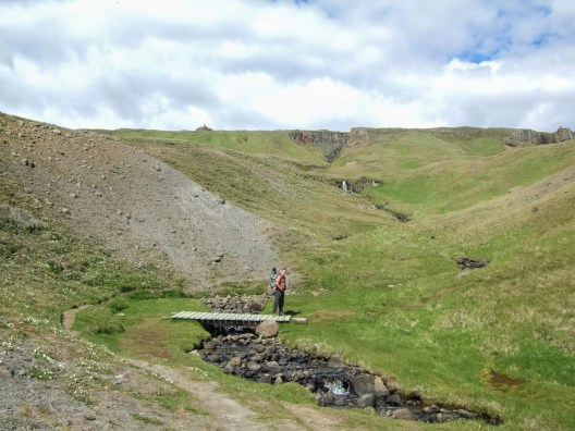 A man crosses a bridge on a hike up a waterfall - An Epic 14 Day Iceland Itinerary