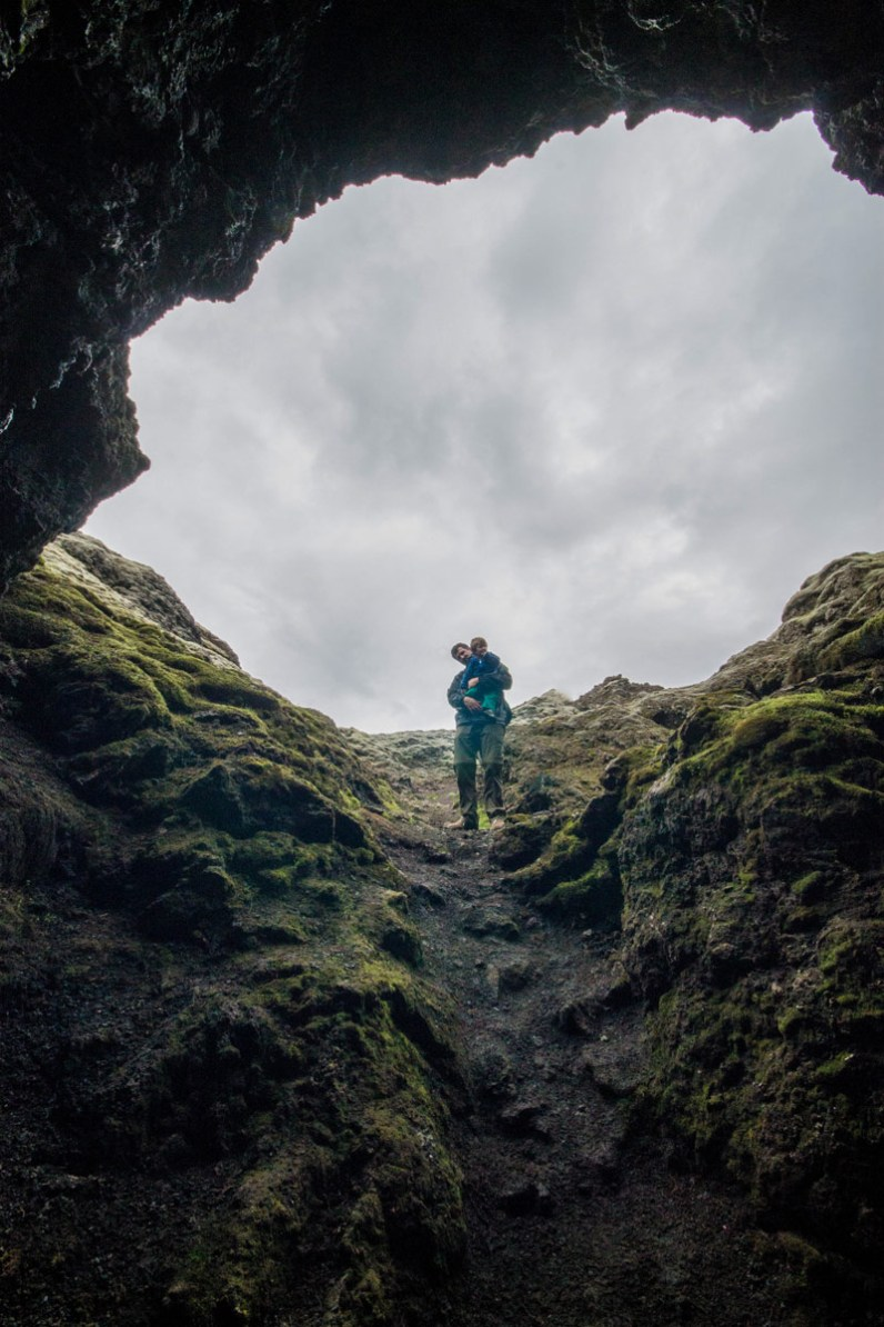 A father and son are silhouetted against a cave entrance - An Epic 14 Day Iceland Itinerary