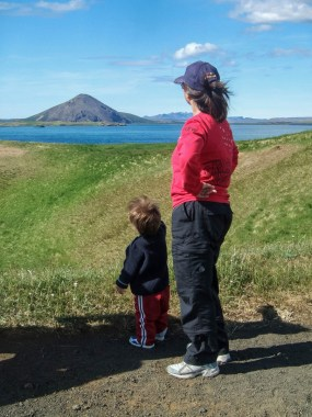 A mother and young boy look at volcanic mountains in a lake - An Epic 14 Day Iceland Itinerary