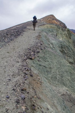 A man carrying a kid-carrier hikes up a steep hill - An Epic 14 Day Iceland Itinerary