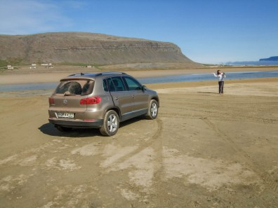 A woman waves in the distance towards an SUV parked on an Icelandic beach - An Epic 14 Day Iceland Itinerary