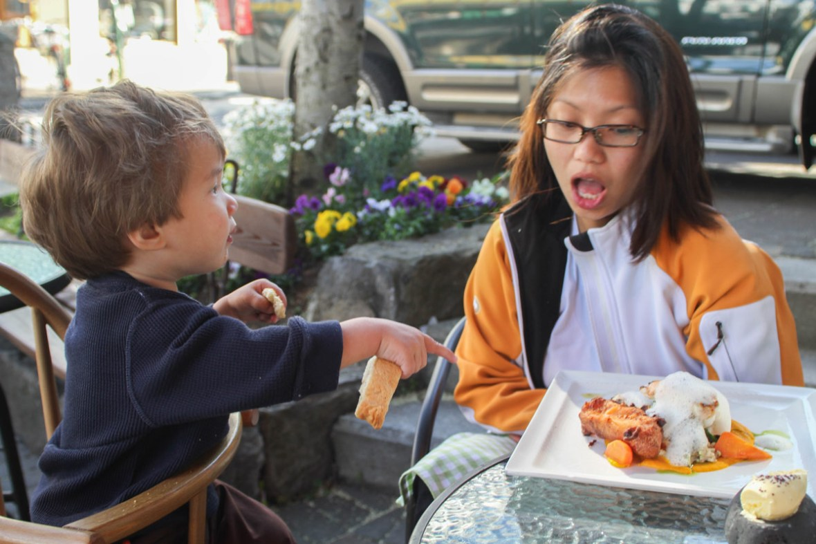 A young boy laughs and points at a plate of food on the patio of an icelandic restaurant