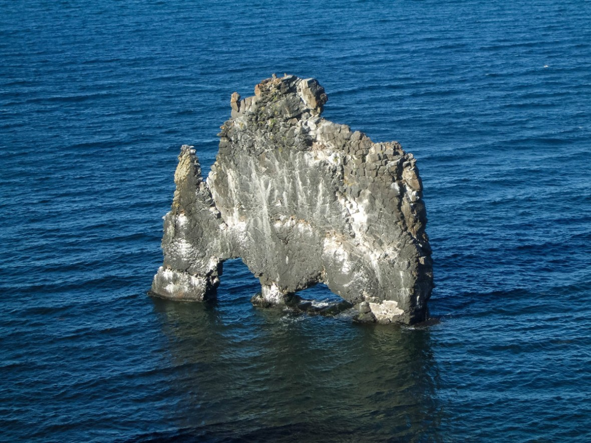A large, thin rock with two arches sits in the water off Icelands Vatnsnes-peninsula - An Epic 14 Day Iceland Itinerary