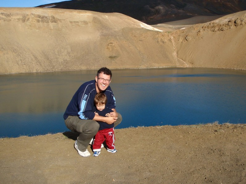 A father and son pose next to a volcanic crater lake in Iceland - An Epic 14 Day Iceland Itinerary