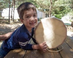 Boy happily poses with the drum he just made as part of the Great Spirit Circle Trail Make and Take Experience on Manitoulin Island.