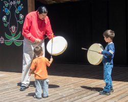 Elder teaches boys some of the intricacies of drumming as part of the Great Spirit Trail Voice of the Drum Make and Take Experience on Manitoulin Island.