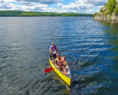 An aerial shot of a family canoeing across a lake - Top things to do in Bon Echo Provincial Park
