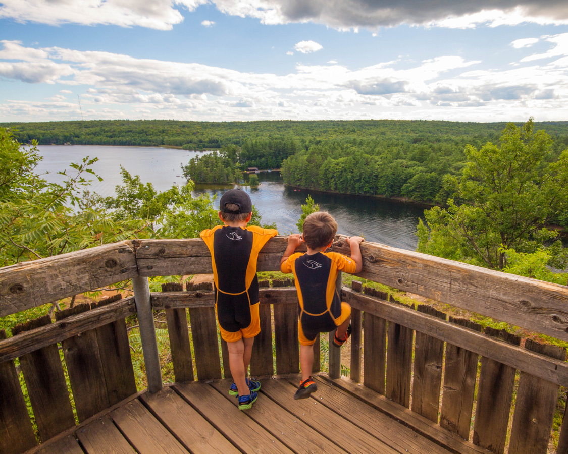 Two young boys wearing wet suits look over a railing at the lagoon in Bon Echo - Top things to do in Bon Echo Provincial Park