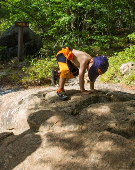 a toddler scrambles over some rocks - Top things to do in Bon Echo Provincial Park