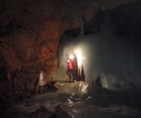 A guide holding a light shows up ice formations inside a cave - caves you can visit with kids