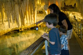 A mother points to rock formations inside a cave to two young boys - caves you can visit with kids