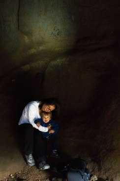 A mother snuggles her young son in Songhellir cave in Iceland - CAves you can visit with kids