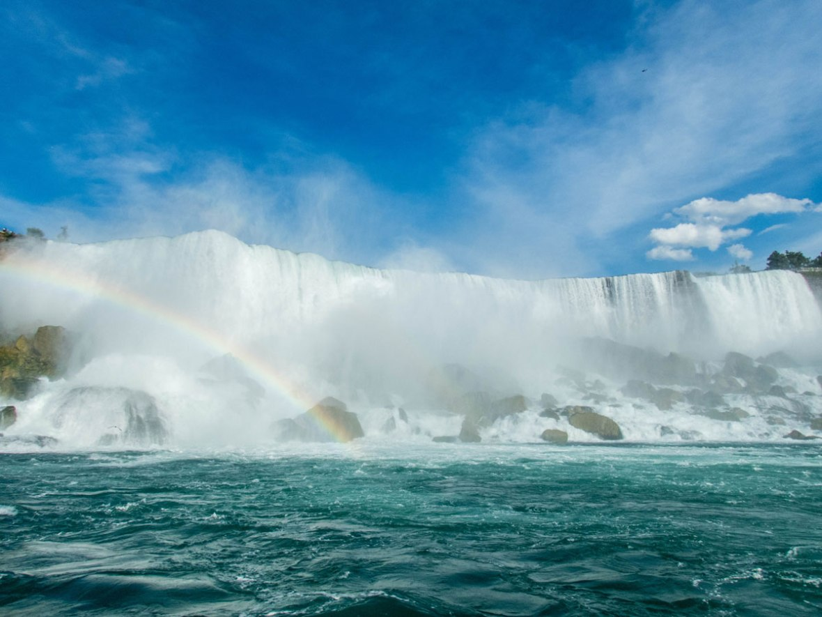 A rainbow on the side of a rocky American Falls - Exploring Niagara Falls