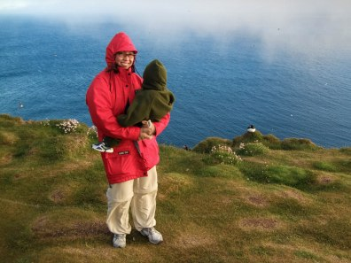 A mother in a red rain jacket holds a young child at the Latrabjarg Puffin Cliffs