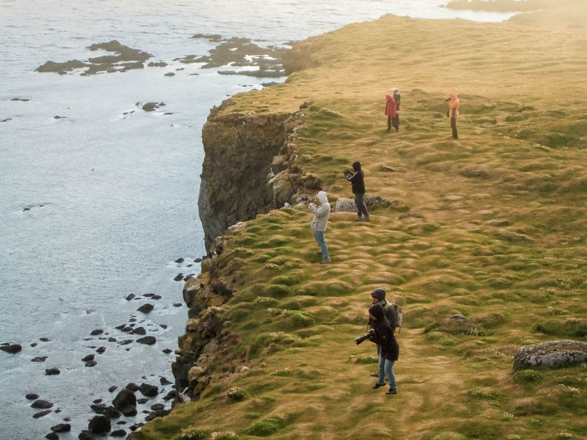 Photographers take in the sunset at the Latrabjarg Puffin Cliffs in Iceland