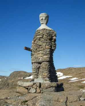 a tall viking statue made of layered stones stands beside a road in Iceland