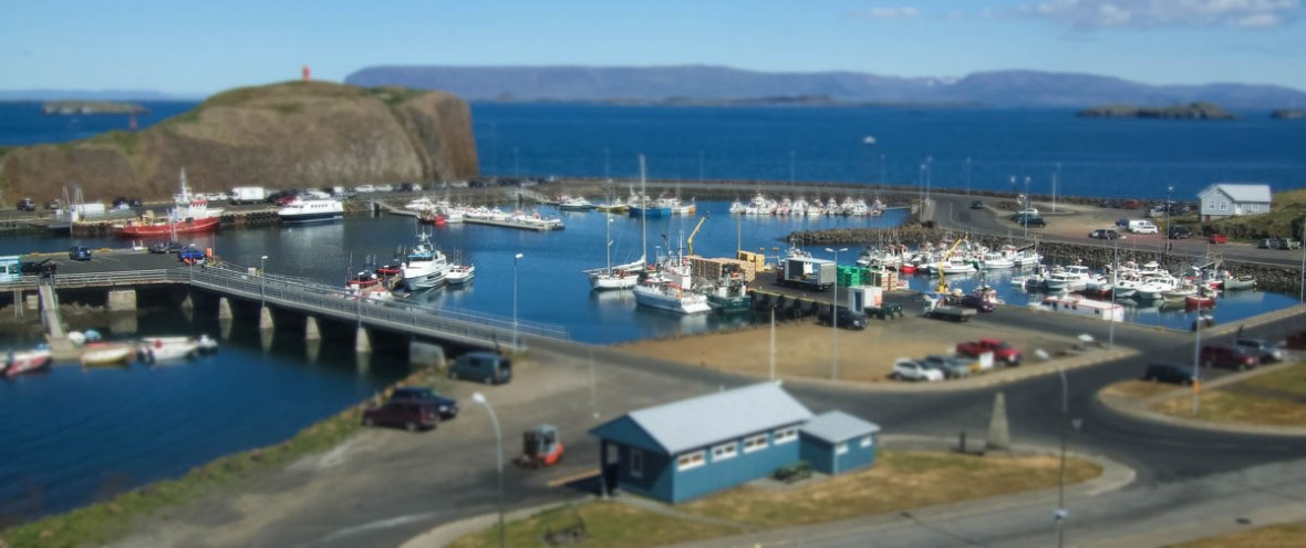 A small fishing town in Iceland with quaint buildings and fishing boats throughout a marina