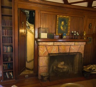 A hidden door in the panel of the library at Singer Castle.