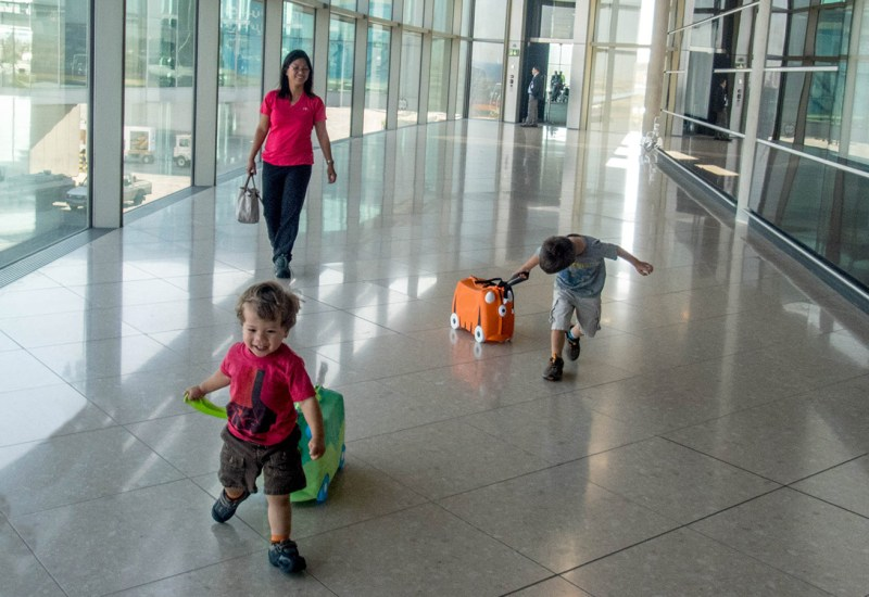A woman and two young boys run through an airport