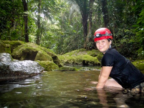 Women getting ready to cross a stream as part of the caving experience at ATM one of the must do activities in Belize.