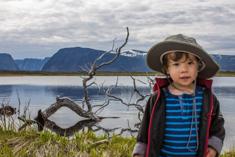 A young boy in explorer gear poses in front of Western Brook Pond in Newfounland