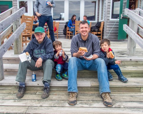 A grandmother, father and two young boys eat hot dogs on a set of stairs