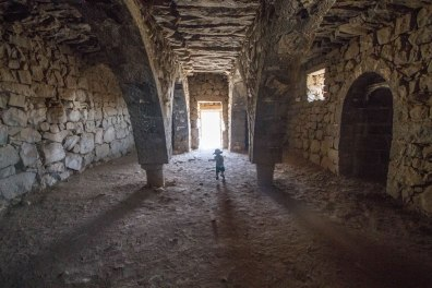 A young boy walks through the domed arches of Azraq Castle in Jordan