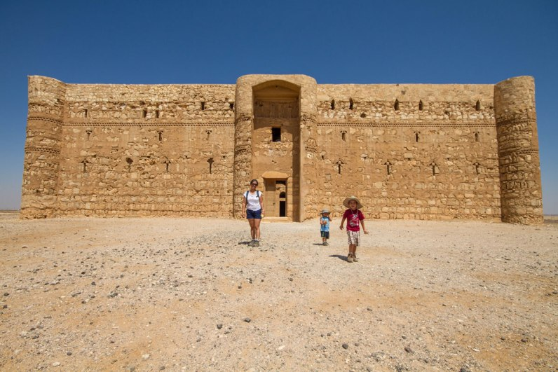 A woman and two young boys walk out of one of the desert castles in Jordan