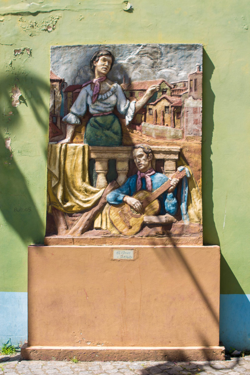 Art of woman singing and man playing a guitar on a street wall in El Caminito in La Boca district.