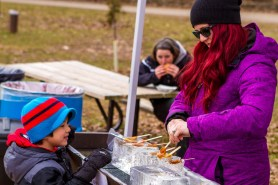 A young boy lines up for some maple taffy at the Terra Cotta Maple Festival