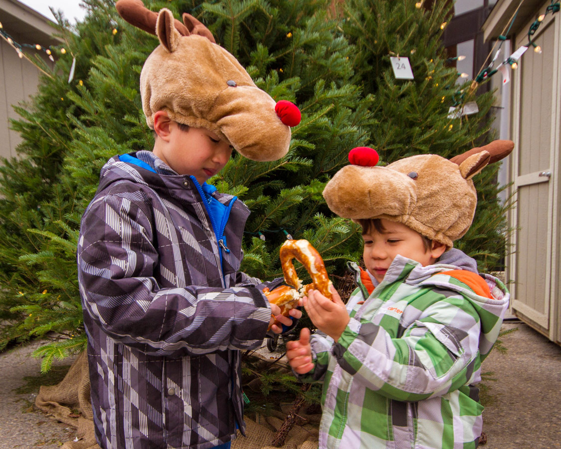Two young boys wearing reindeer hats eat a pretzel in front of a christmas tree at the Christkindle Christmas Market in Kitchener, Ontario
