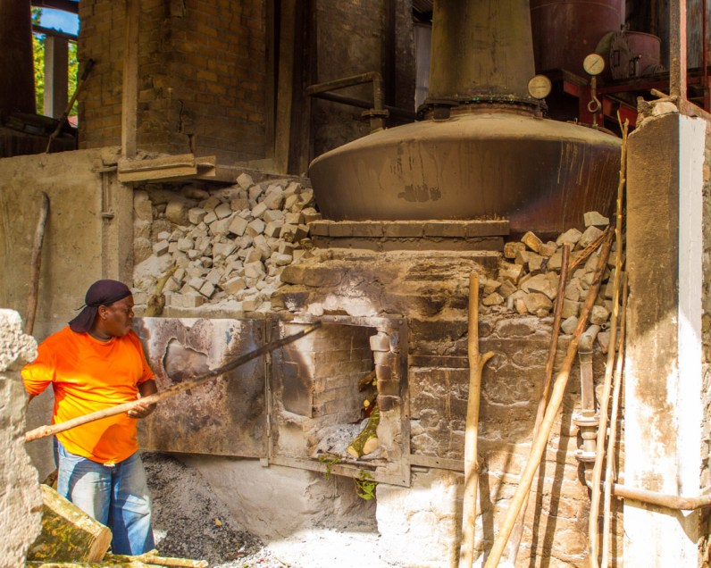 A Caribbean rum worker stokes a large antique boiler by hand at the River Antoine Rum Distillery in Grenada