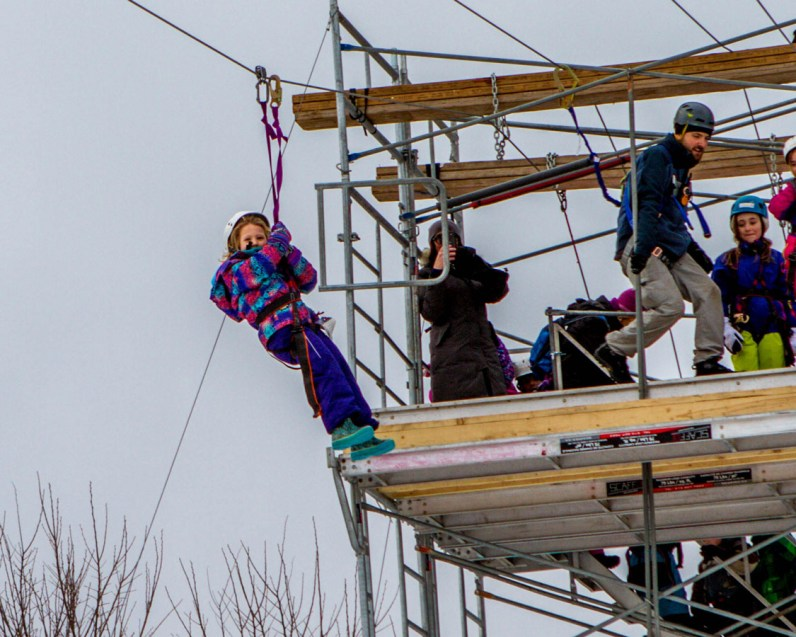 Girl gets ready to go on a zip line.