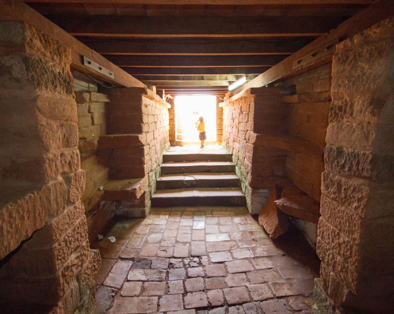 A young boy stands at the entrace of a crypt in the Jesuit ruins in Paraguay