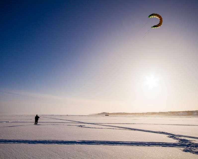 Man kite flying in winter on Great Slave Lake, Yellowknife.