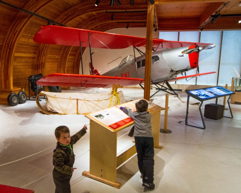 Two boys look at old sleds and aircraft at the Prince of Wales Northern Heritage Center in Yellowknife.