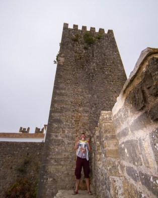 A father and baby wave to the camera along the castle walls of Obidos, Portugal