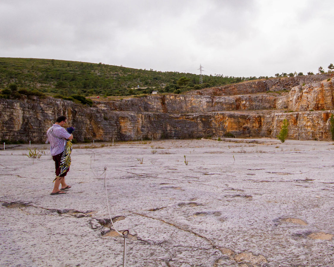 a man carrying a baby through a quarry filled with fossilised dinosaur footprints as a day trip from Fatima, Ourem and Obidos