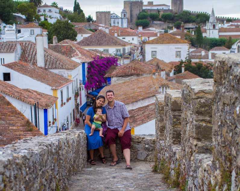A family takes a photo overlooking the walled city of Obidos, Portugal