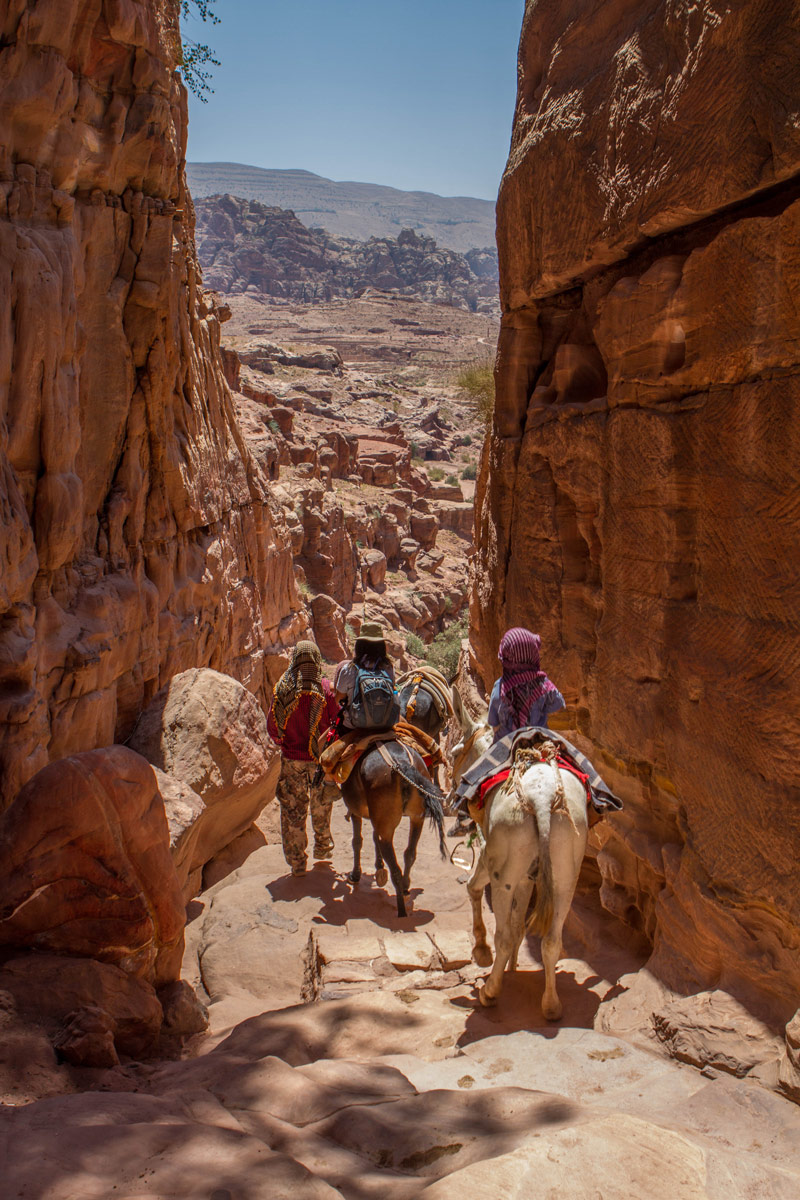 a family on horseback rides through tall cliffs on the way down from the Monastery