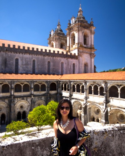 Woman on upper level of The cloister in the Monastery of Alcobaca, Portugal.