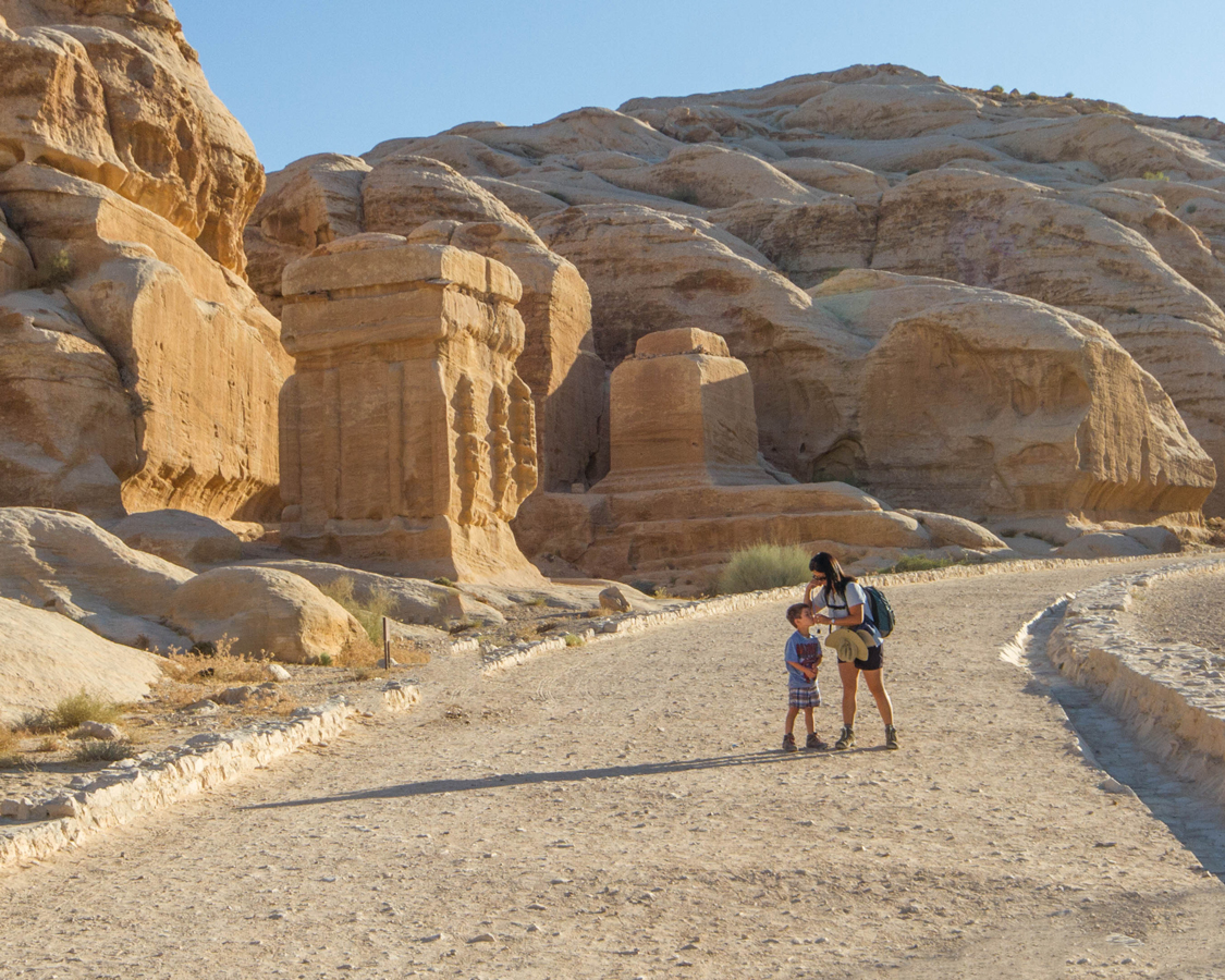 A mother and son explore the columns lining the pathway to al siq in Petra Jordan as they explore what to see in Jordan with kids