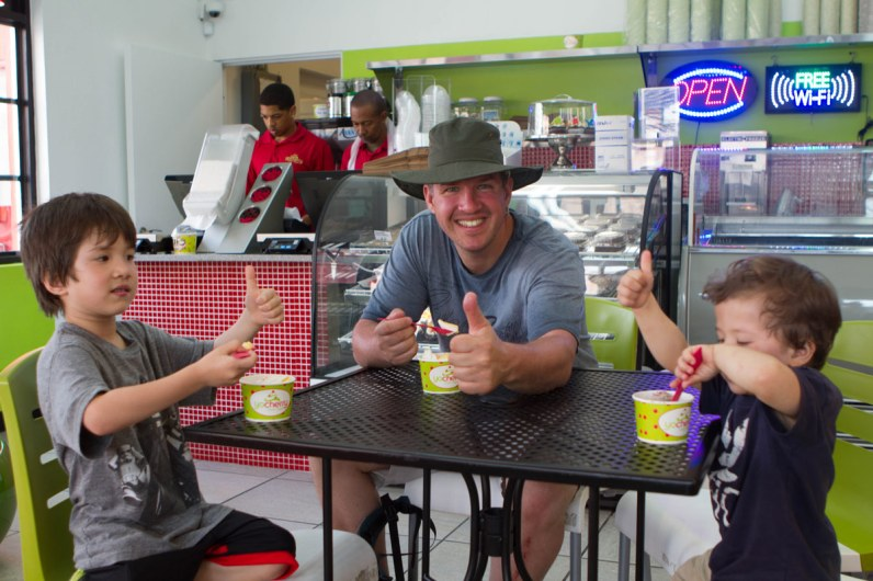 Man with two boys sitting down and having frozen yogurt in St George Bermuda.