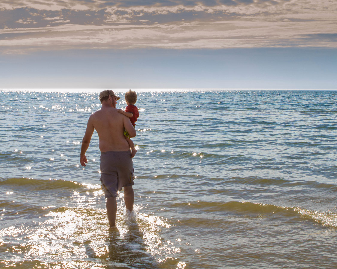 Father carries son into the waters of Sauble Beach, Ontario.