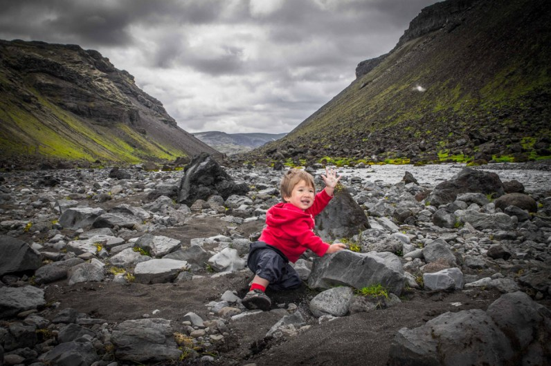 A toddler takes a break during a hike along Eldja Canyon to splash happily in the water in Iceland