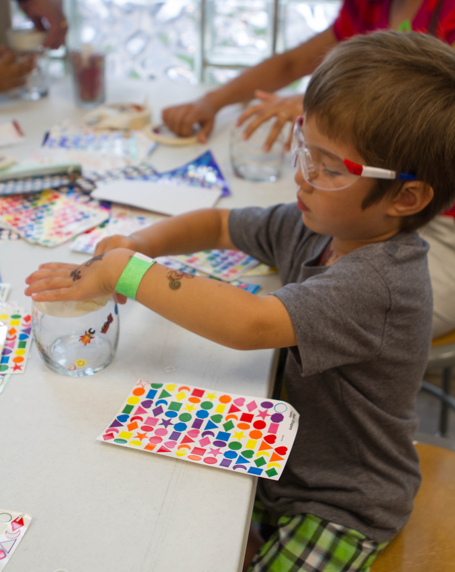 Boy adding stickers to his candle holder during the Glass Blowing Workshop at the Corning Museum of Glass.