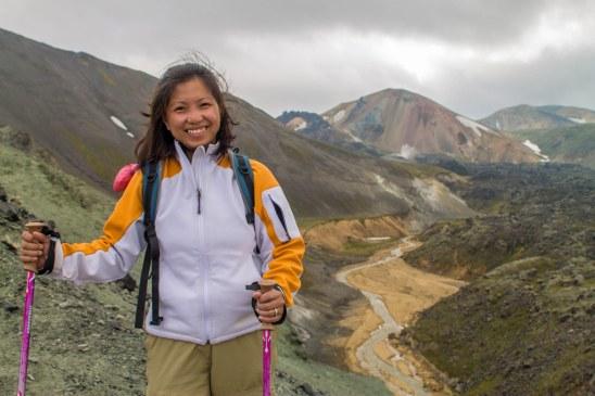 A smiling asian woman hikes through Landmannalaugar in Iceland