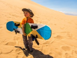 A toddler carries a sandboard through the desert while sandboarding with kids in Peru