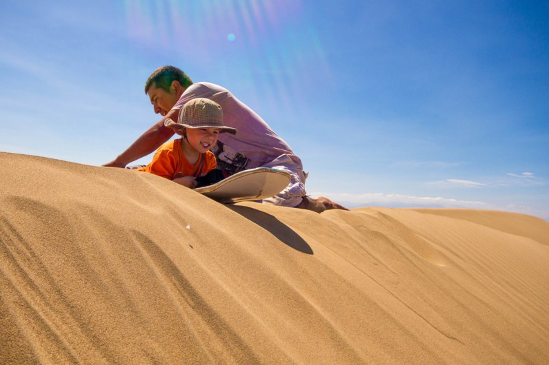 A toddler prepares to go sandboarding in Peru with Kids near Huacachina