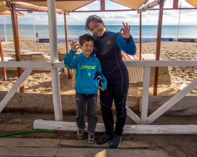 A woman wearing a wetsuit hugs her son while they both give OK signs with their fingers as they prepare to go Scuba diving with sea lions in Punta Loma